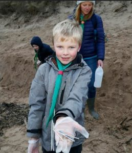 A member of the Gullane Beaver Scout Group finds cotton buds with plastic stems on Scotland's Gullane Beach, January 11, 2018 (Photo by Scottish Government) Creative Commons license via Flickr