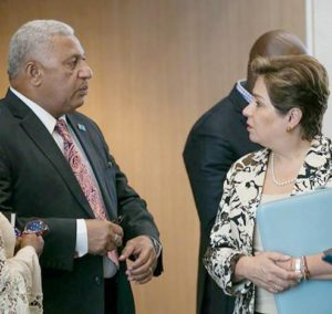Prime Minister Frank Bainimarama, and COP 23 President, Fiji, and UNFCCC Executive Secretary Patricia Espinosa speak in a hallway at the Bonn Climate Conference, May 7, 2018 (Photo courtesy Earth Negotiations Bulletin) Used with permission