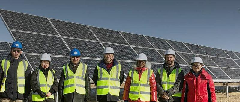 Workers who helped install Mongolia's largest solar energy farm in the Sumber Soum area of the country's Govisümber province with a few of the solar panels they put in place. The solar facility began generating power on January 28, 2019. (Photo courtesy Green Climate Fund) Posted for media use.