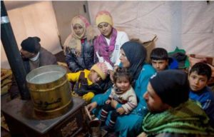 Members of a Syrian refugee family huddle around a stove inside their shelter in Lebanon's Bekaa Valley. 2013 (Photo by A. McConnell courtesy UNHCR) Posted for media use